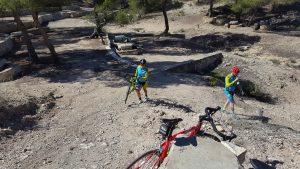 Ciclista con la bici a cuestas en Fuente de la Higuera en Sierra de la Pila por Comunidad Biker MTB