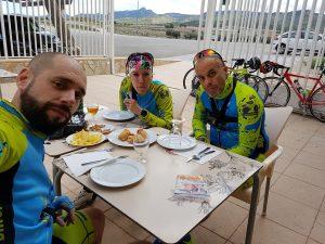 Ciclistas comiendo en bar para descansar del viento cerca de la Sierra de la Pila por Comunidad Biker MTB